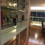 Bar com revestimento de espelho com jato desenhado, pratelerias em vidro incolor de 19mm de espessura e portas de abrir