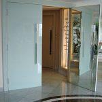 Porta de entrada revestida com vidro serigrafado branco do lado interno e espelho pelo lado externo
